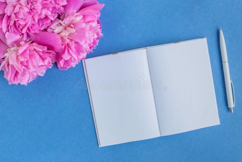 Modelnotitieboekje met roze pioenen stock foto