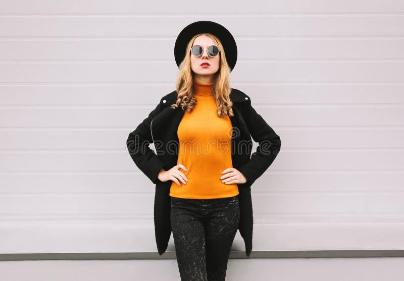 Modelo à moda da jovem mulher que veste a roupa preta do estilo, revestimento, chapéu redondo, levantando na rua da cidade fotografia de stock