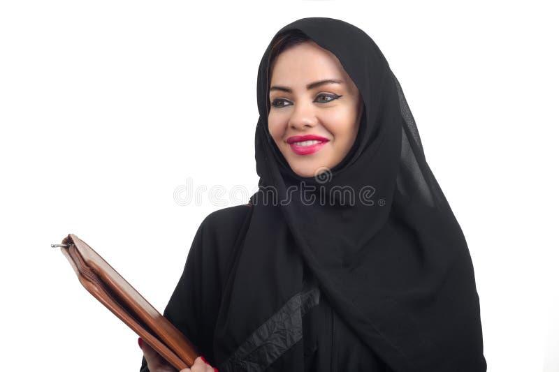 Modelo árabe bonito no hijab que mantém um dobrador isolado no whit foto de stock royalty free