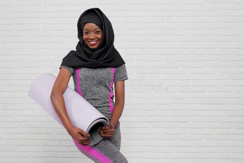 Modelo africano atlético que presenta con la estera para los ejercicios fotografía de archivo