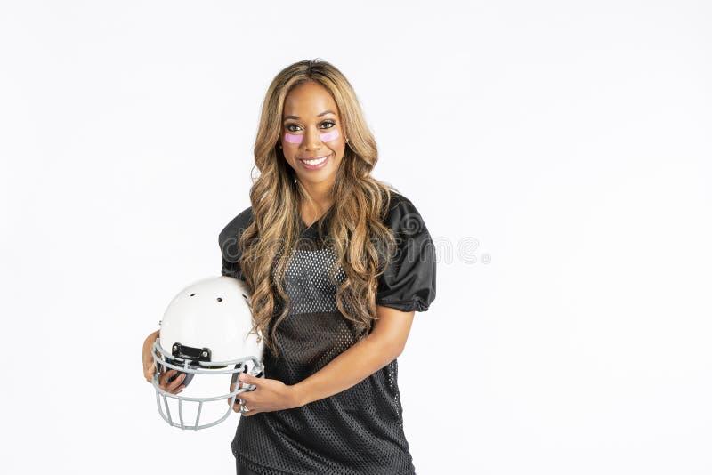 Modelo afro-americano bonito Wearing um capacete de futebol e guardar um futebol foto de stock royalty free