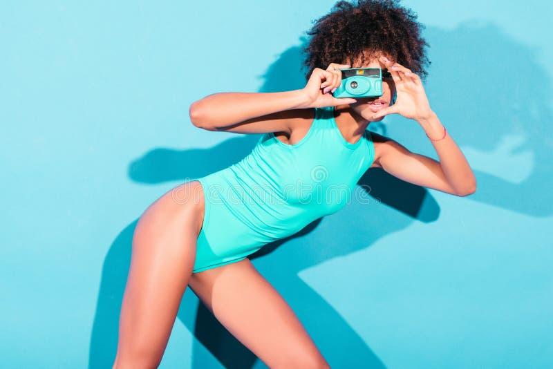 modelo afro elegante atrativo que levanta no roupa de banho azul com a câmera da foto do vintage, imagens de stock