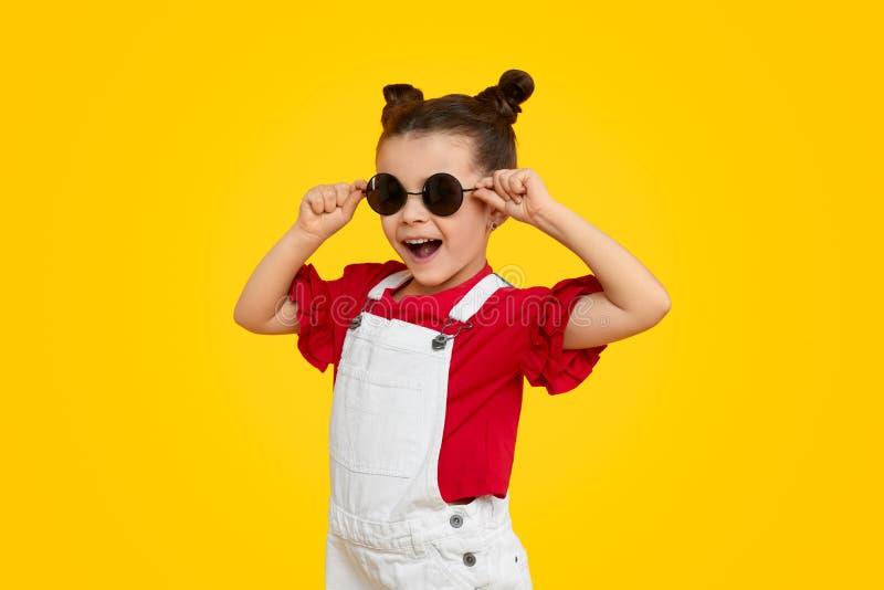 Modelo alegre da criança que tenta em óculos de sol à moda fotos de stock
