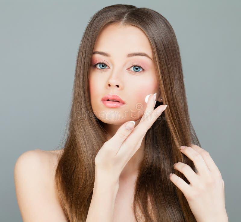 Modelo Applies dos termas da mulher um creme hidratante a sua cara fotografia de stock