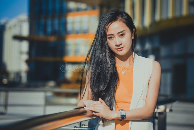 Modelo asiático hermoso de la muchacha en el vestido blanco que presenta en el fondo de cristal moderno de la ciudad de la oficin imágenes de archivo libres de regalías
