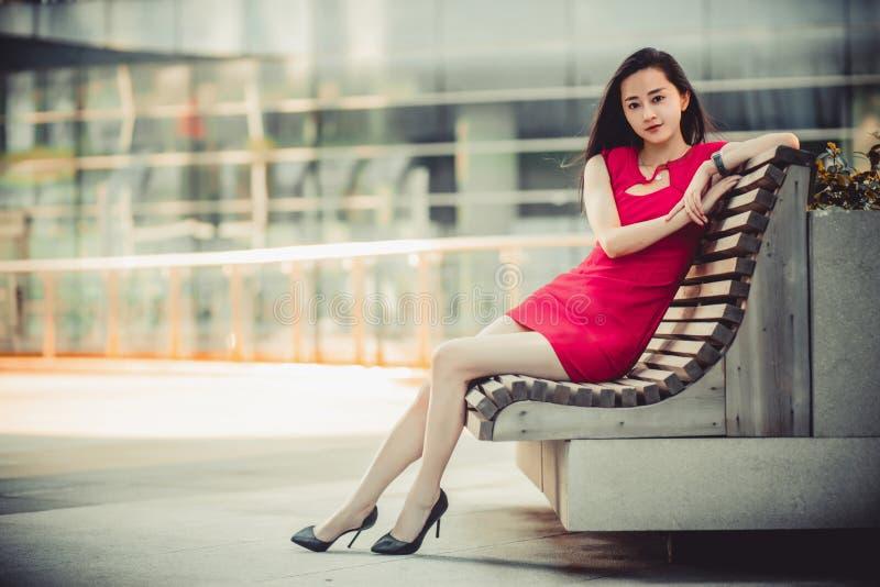 Modelo asiático hermoso de la muchacha en el vestido rojo que se sienta en un banco que presenta en el fondo moderno de la ciudad fotografía de archivo libre de regalías