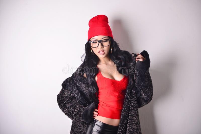 Modelo asiático na blusa vermelha, casaco de pele, tampão vermelho, vidros, busto imagens de stock royalty free