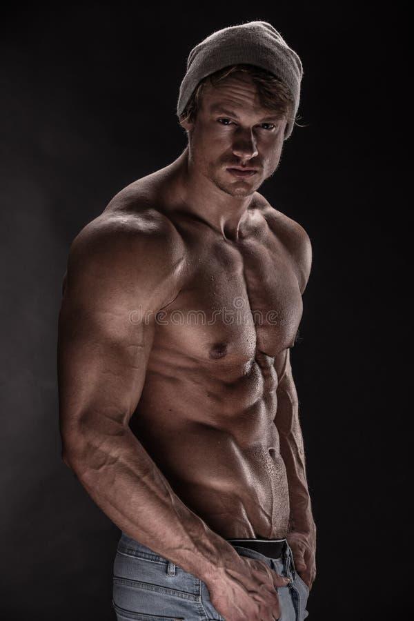 Modelo atlético forte da aptidão do homem no fundo preto fotos de stock royalty free