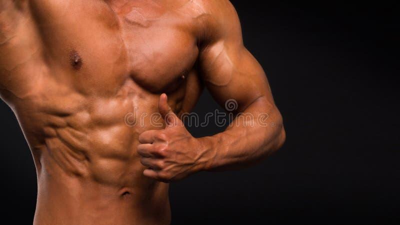 Modelo atlético forte Torso da aptidão do homem que mostra seis Abs do bloco no fundo escuro foto de stock royalty free