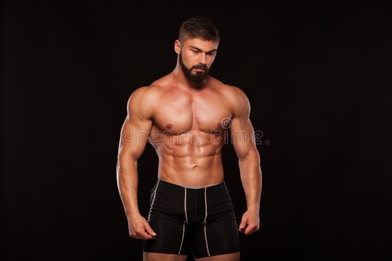 Modelo atlético forte Torso da aptidão do homem que mostra seis Abs do bloco Isolado no fundo preto com Copyspace imagem de stock royalty free