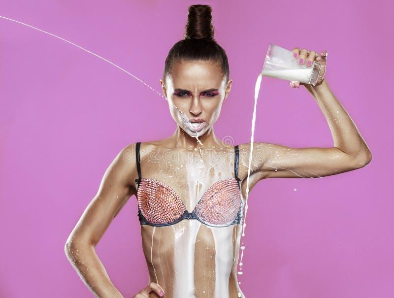 Modelo atractivo con el chapoteo de la leche imagen de archivo
