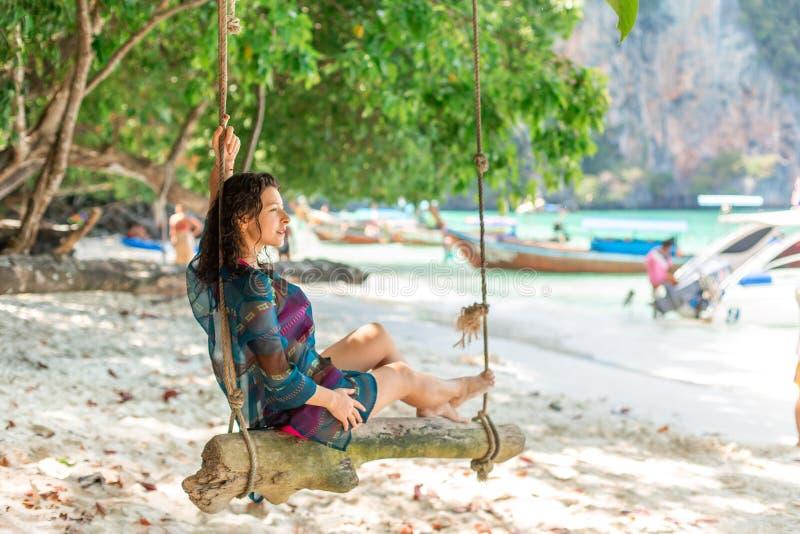 Modelo atractivo delgado de la muchacha en un traje de baño que presenta en un oscilación de madera atado a un árbol En el fondo  fotos de archivo