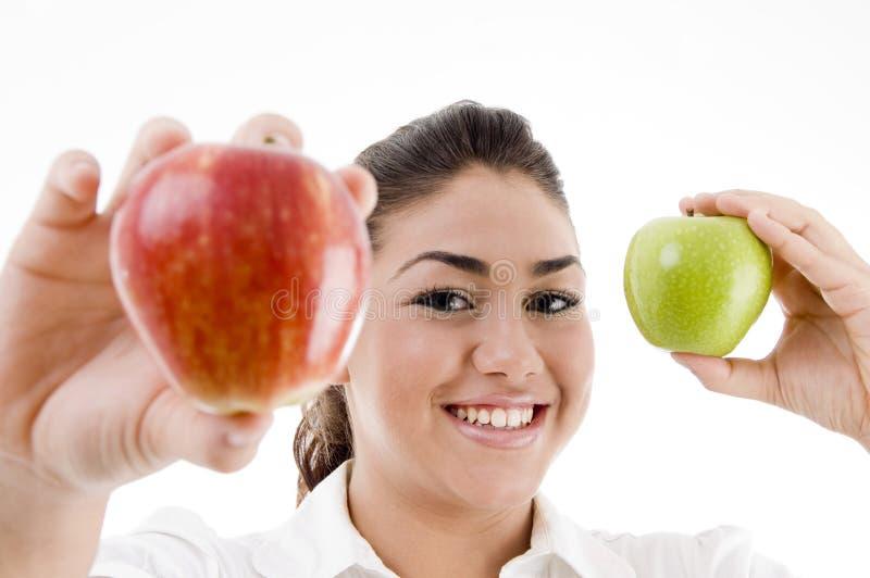 Modelo atractivo joven que muestra la manzana verde y roja fotos de archivo