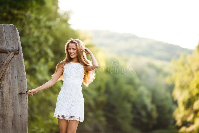 Modelo atractivo sonriente de pelo largo encantador de la muchacha morena feliz en un paseo blanco del vestido por el río fotografía de archivo