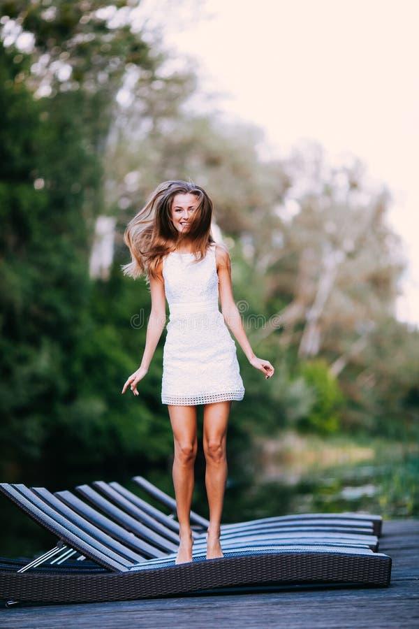 Modelo atractivo sonriente de pelo largo encantador de la muchacha morena feliz en un paseo blanco del vestido por el río fotografía de archivo libre de regalías