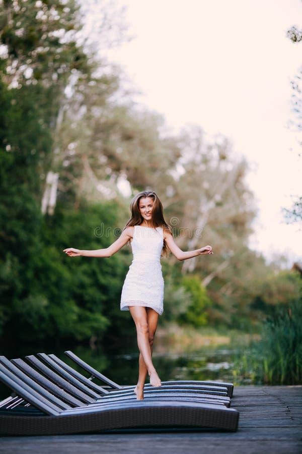 Modelo atractivo sonriente de pelo largo encantador de la muchacha morena feliz en un paseo blanco del vestido por el río fotos de archivo