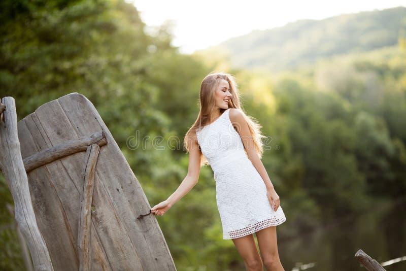 Modelo atractivo sonriente de pelo largo encantador de la muchacha morena feliz en un paseo blanco del vestido por el río imágenes de archivo libres de regalías