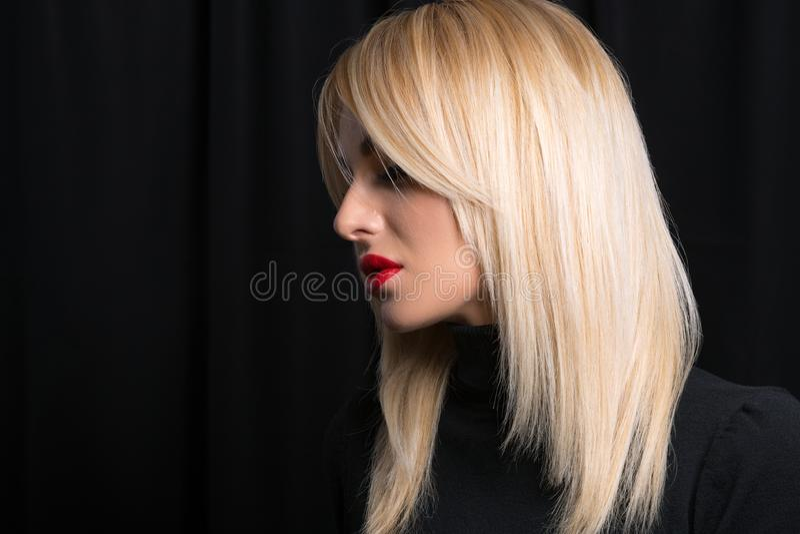 Modelo atractivo y hermoso con el pelo rubio directo en fondo negro Labios pintados con lipstic rojo fotografía de archivo libre de regalías