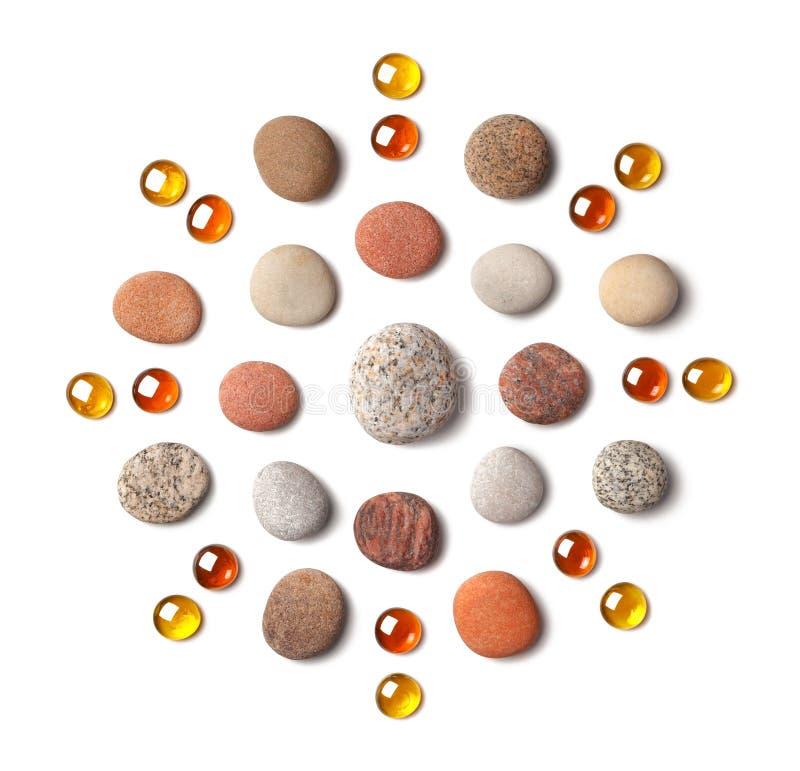 Modelo bajo la forma de círculo de guijarros coloreados y de cuentas de cristal anaranjadas aislados en el fondo blanco imagen de archivo