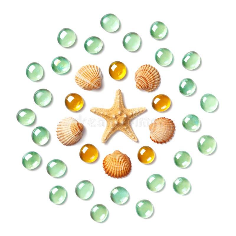 Modelo bajo la forma de círculo hecho de las cáscaras, de las estrellas de mar y de las cuentas de cristal verdes y amarillas ais fotografía de archivo libre de regalías