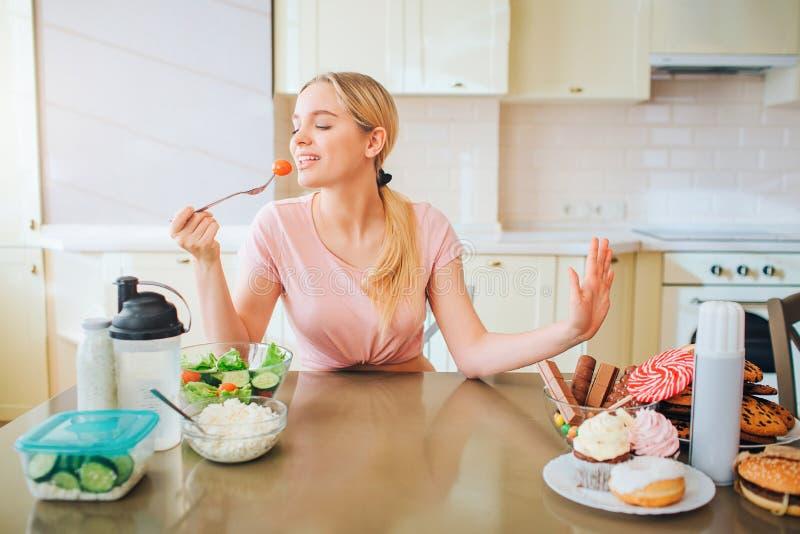Modelo bem-construído novo agradável que eting o alimento saudável na cozinha na tabela Diz não à refeição da sucata Apenas na co fotografia de stock