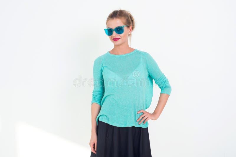 Modelo bonito apto que levanta com os óculos de sol no estúdio no fundo branco Retrato de uma jovem mulher em vestir imagem de stock