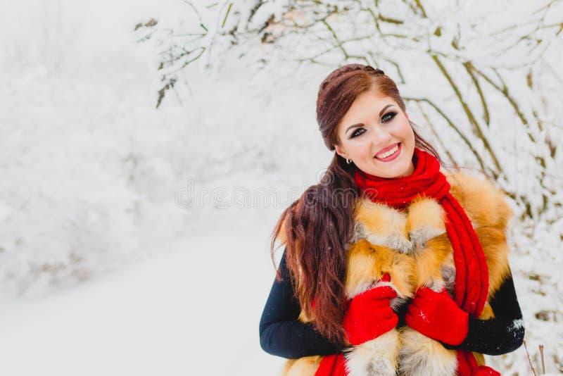 Modelo bonito con el pelo rojo que presenta en bosque del invierno imágenes de archivo libres de regalías