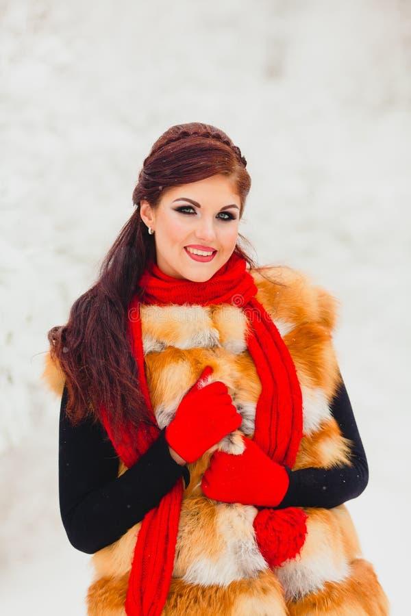 Modelo bonito con el pelo rojo que presenta en bosque del invierno imagen de archivo
