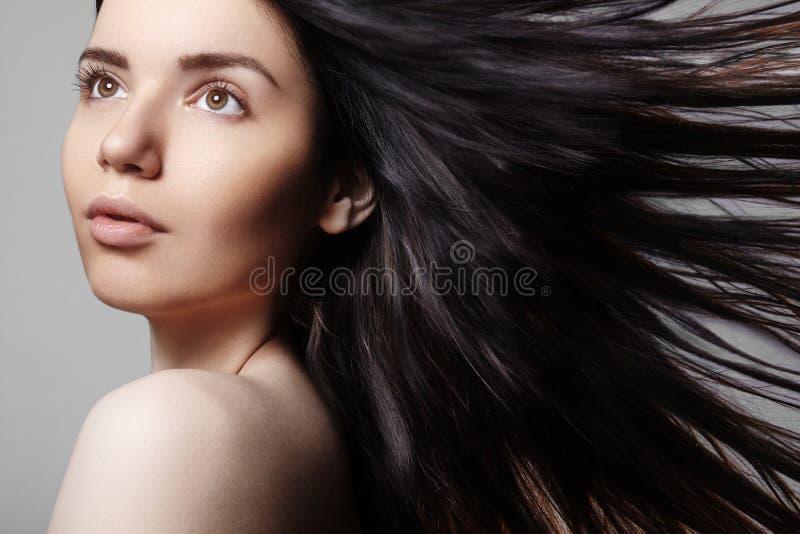 Modelo bonito da jovem mulher com voo do cabelo marrom da cor Compõe, penteado encaracolado Haircare, composição imagens de stock