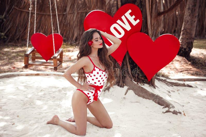 Modelo bonito bonito da menina no roupa de banho do estilo do pinup que levanta na areia branca, sobre cora??es Conceito de Maldi fotos de stock royalty free
