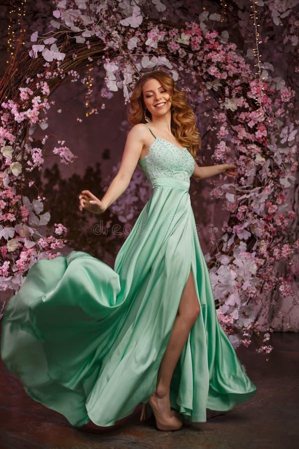 Modelo bonito da mulher em um vestido hortelã-colorido em um fundo florescido da mola Menina da beleza com uma composição e um pe imagens de stock