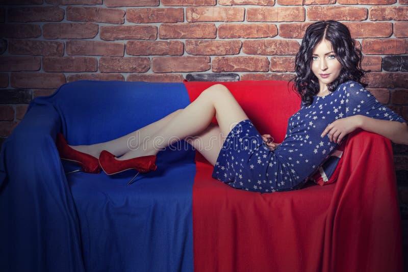 Modelo bonito da mulher no sofá no vestido em t azul e vermelho imagem de stock royalty free