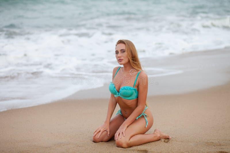 Modelo bonito do biquini com o cabelo louro longo que senta-se na praia do mar vietnam foto de stock
