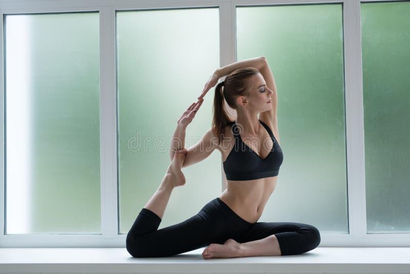 Modelo bonito no peitoril da janela na pose da ioga fotos de stock royalty free