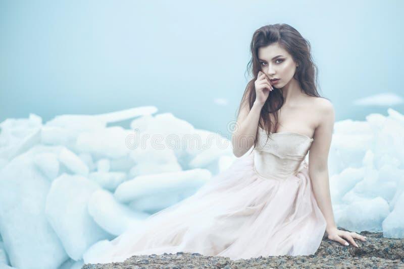 Modelo bonito novo no vestido de bola sem alças luxuoso do espartilho que senta-se em lajes de gelo quebrado no beira-mar enevoad foto de stock royalty free