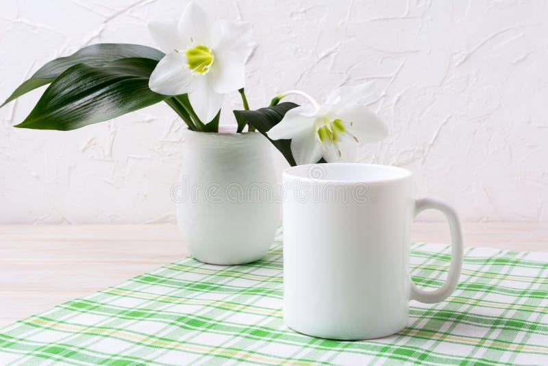Modelo branco da caneca com o lírio no vaso no guardanapo quadriculado verde imagens de stock royalty free