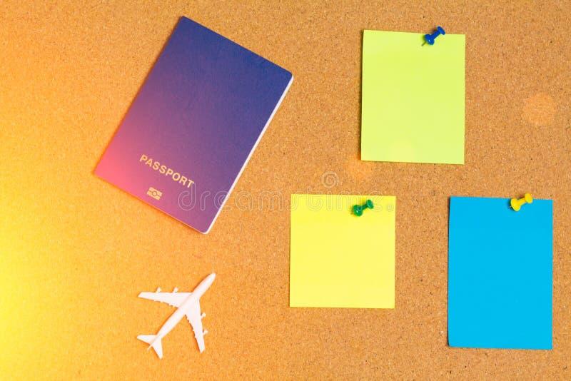 Modelo branco do avião comercial com passaporte azul e do pino de papel azul, alaranjado, amarelo da nota na placa da cortiça As  fotografia de stock