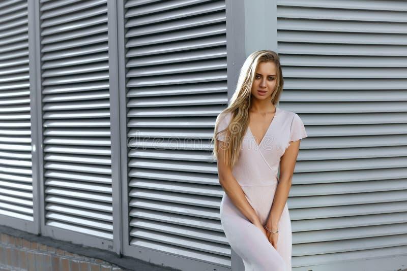 Modelo bronceado atractivo en el equipo de moda que presenta en el backg fotografía de archivo