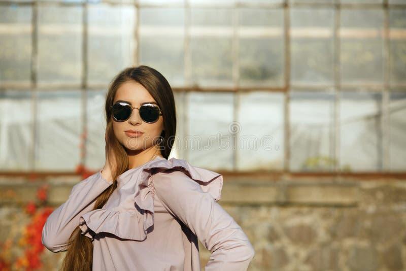 Modelo bronzeado elegante que veste vidros na moda da blusa e do espelho, levantamento exterior com luz do sol Espaço vazio imagens de stock