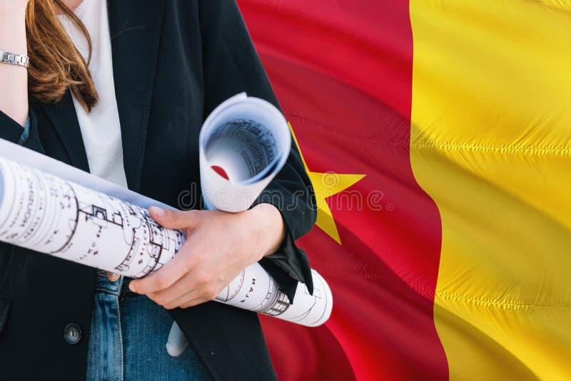 Modelo camerunés de la tenencia de la mujer del arquitecto contra fondo de la bandera del Camerún que agita Concepto de la constr foto de archivo libre de regalías