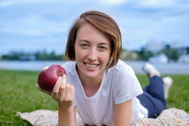 Modelo caucásico muy hermoso que come la manzana roja en el parque Al aire libre retrato de la chica joven bonita fotografía de archivo