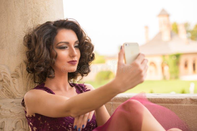 Modelo caucasiano sensual com o takin do cabelo encaracolado e do vestido de cocktail fotos de stock