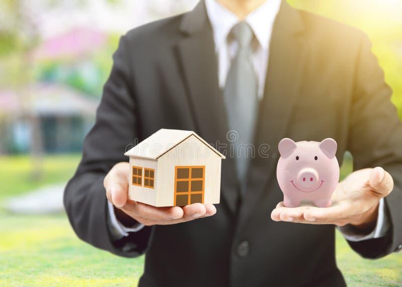 Modelo cerâmico leitão com homem de negócios, seguro do banco e da casa do rosa foto de stock royalty free