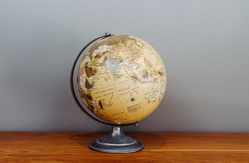 Modelo clásico retro del globo de la escuela del vintage de la tierra en fondo gris del piso de madera foto de archivo libre de regalías