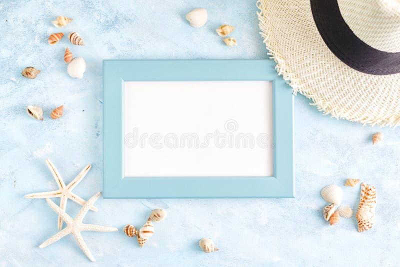 Modelo colocado liso do verão da vista superior: quadro da foto, conchas do mar, chapéu de palha e estrela do mar azuis vazios no imagem de stock