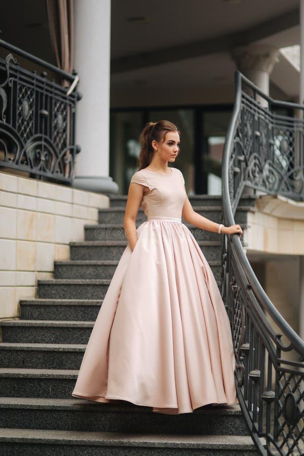 Modelo com cabelo moreno em um vestido da cor do pó e com composição da noite foto de stock royalty free