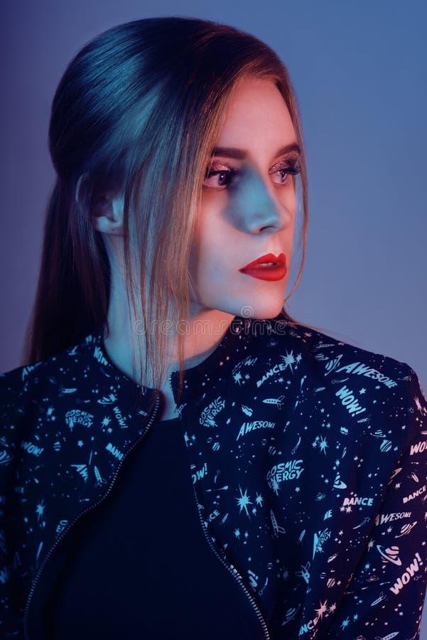 Modelo com estilo do ar Mulher nas luzes brilhantes coloridas que levantam no estúdio, retrato da menina bonita com composição na imagens de stock