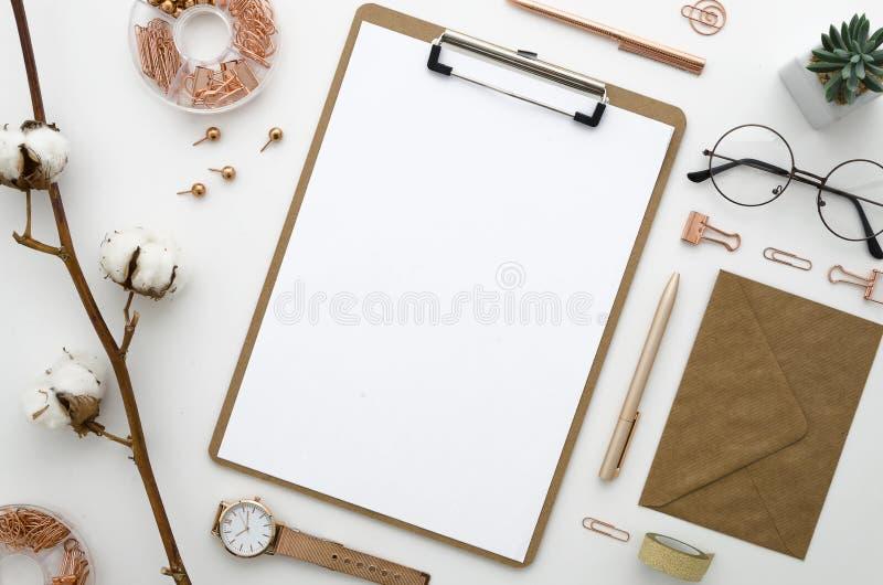 Modelo com o envelope, a placa de grampo, as flores do algodão, os vidros e os acessórios dourados arranjados e pedidos Escritóri fotografia de stock