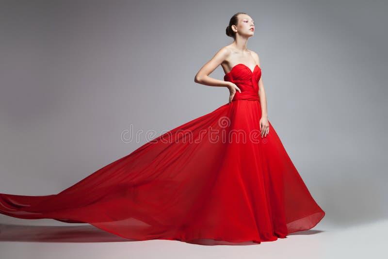 Modelo com a saia do voo do vestido vermelho fotos de stock royalty free