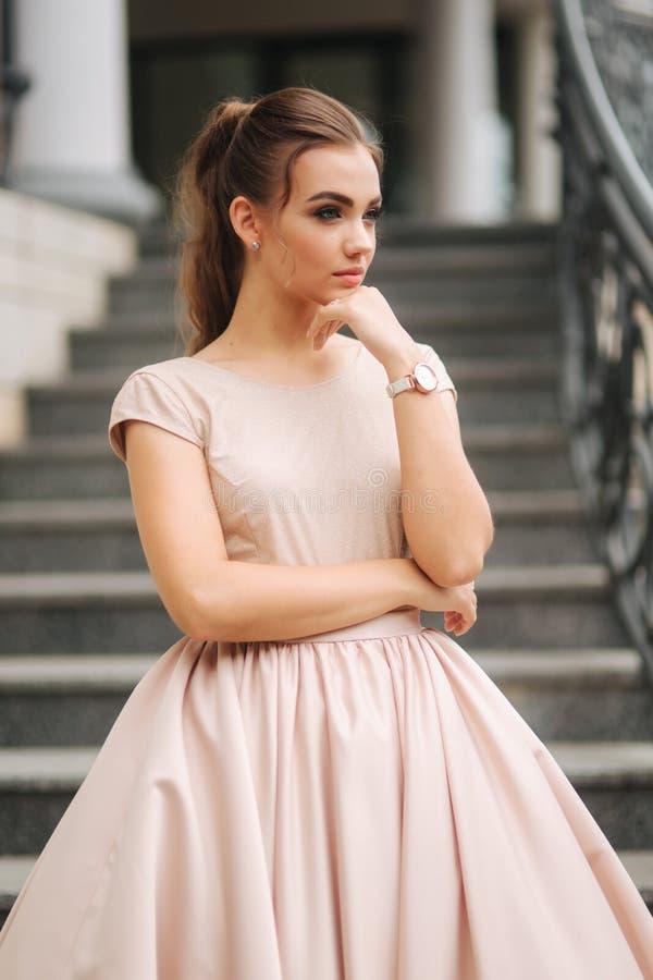 Modelo con el pelo moreno en un vestido del color del polvo y con maquillaje de la tarde fotografía de archivo